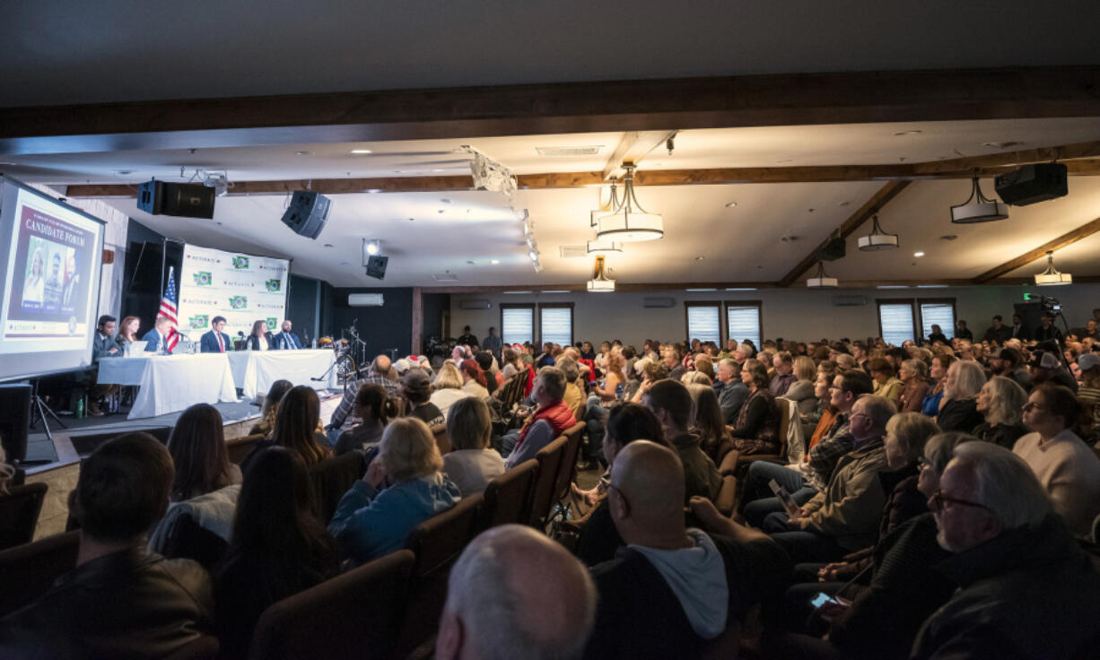 A crowd of more than 200 people listens to opening remarks from candidates running to represent Washington's 3rd Congressional District on Tuesday during a forum at Church on the Rock in Battle Ground.