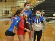 Ridgefield seniors (from left) Presley McCaskill, Emilea Stepaniuk, Allie Andrew and Kohana Fukuchi posed with the district trophy after Ridgefield beat Woodland for the 2A district volleyball title (Tim Martinez / The Columbian)