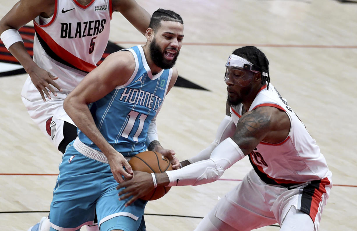 Portland Trail Blazers forward Robert Covington, right, grabs the ball away from Charlotte Hornets forward Cody Martin, left, during the first half of an NBA basketball game in Portland, Ore., Monday, March 1, 2021.