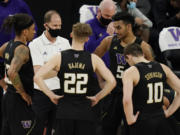 Washington head coach Mike Hopkins speaks with his players during the second half of an NCAA college basketball game in the first round of the Pac-12 men's tournament Wednesday, March 10, 2021, in Las Vegas.