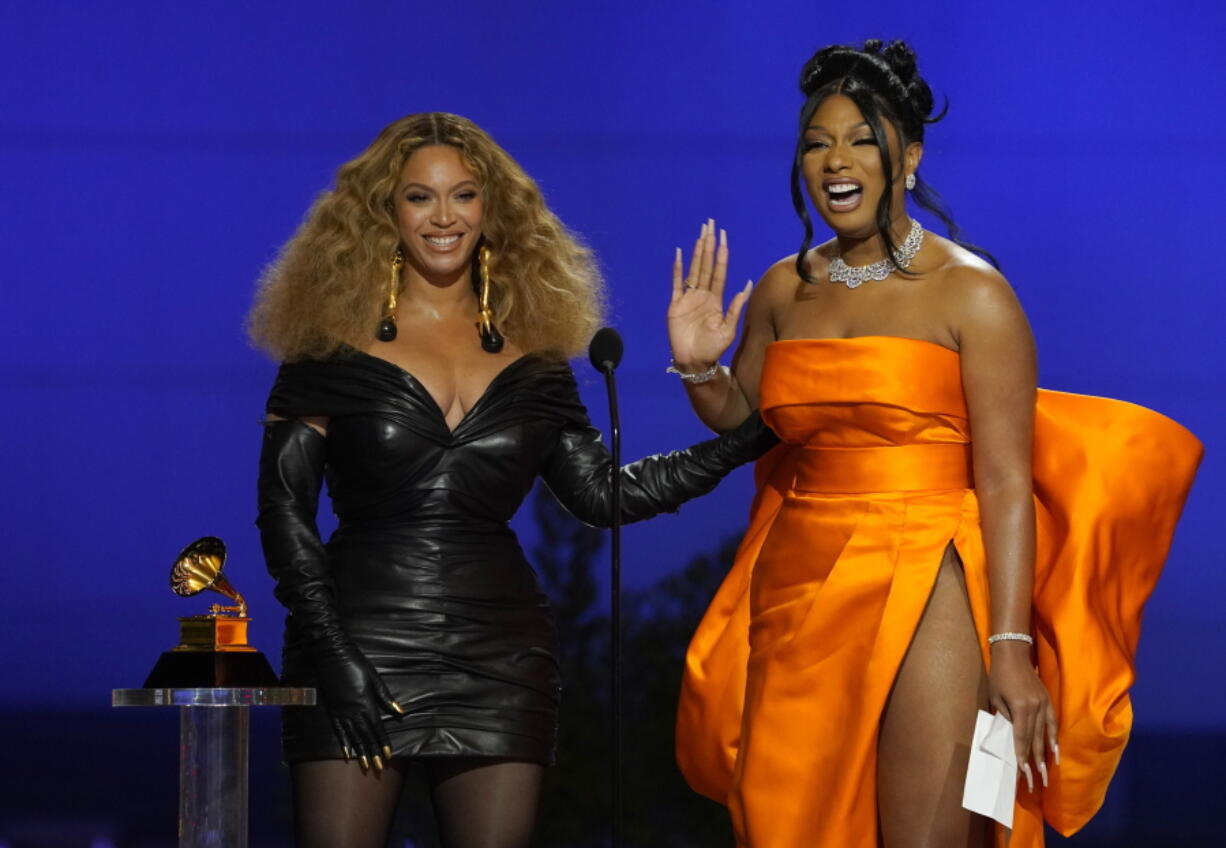 """Beyonce, left, and Megan Thee Stallion accept the award for best rap song for """"Savage"""" at the 63rd annual Grammy Awards at the Los Angeles Convention Center on Sunday, March 14, 2021."""