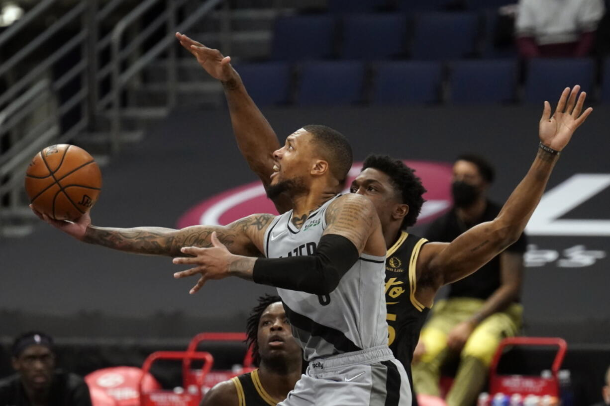 Portland Trail Blazers guard Damian Lillard (0) goes for a layup after getting around Toronto Raptors forward Stanley Johnson (5) during the second half of an NBA basketball game Sunday, March 28, 2021, in Tampa, Fla.