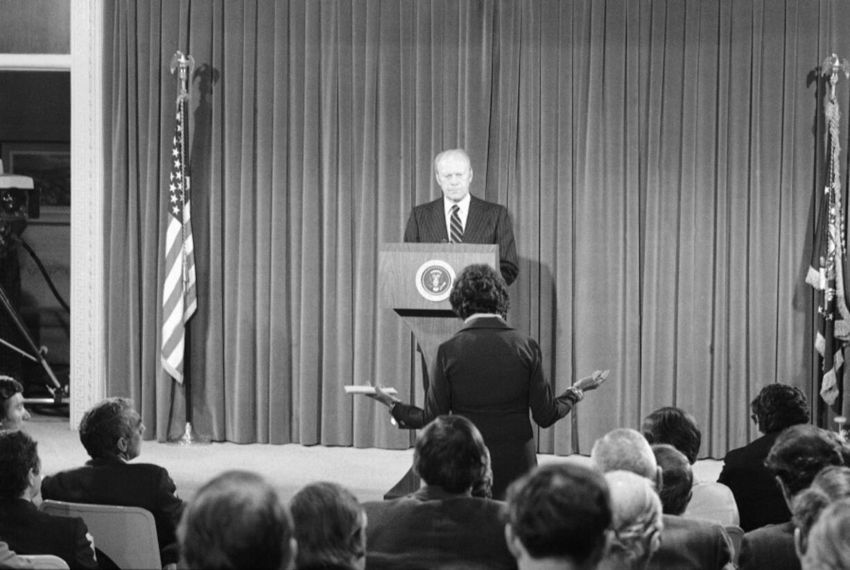 FILE - In this Oct. 9, 1975, file photo President Gerald Ford listens to a news reporter's question during a news conference at the Executive Office building in Washington. It was Ford's first live nationally broadcast news conference since June 24.
