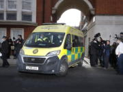 Police officers stand at an entrance to the King Edward VII Hospital where Prince Philip is being treated for an infection, as an ambulance is driven out, in London, Monday, March 1, 2021.