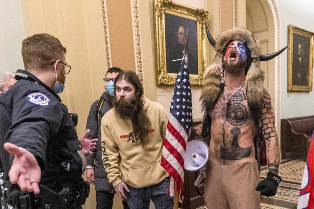 FILE - In this Wednesday, Jan. 6, 2021 file photo, supporters of President Donald Trump, including Jacob Chansley, right with fur hat, are confronted by U.S. Capitol Police officers outside the Senate Chamber inside the Capitol in Washington. Chansley made a written apology from jail, asking for understanding as he was coming to grips with his actions.