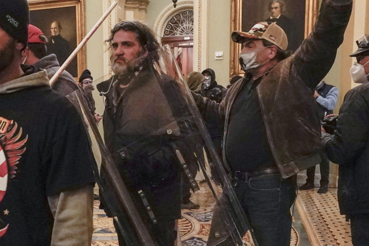In this Jan. 6, 2021, photo, rioters, including Dominic Pezzola, center with police shield, are confronted by U.S. Capitol Police officers outside the Senate Chamber inside the Capitol, Wednesday, Jan. 6, 2021, in Washington. The Proud Boys and Oath Keepers make up a fraction of the more than 300 Trump supporters charged so far in the siege that led to Trump's second impeachment and resulted in the deaths of five people, including a police officer. But several of their leaders, members and associates have become the central targets of the Justice Department's sprawling investigation.