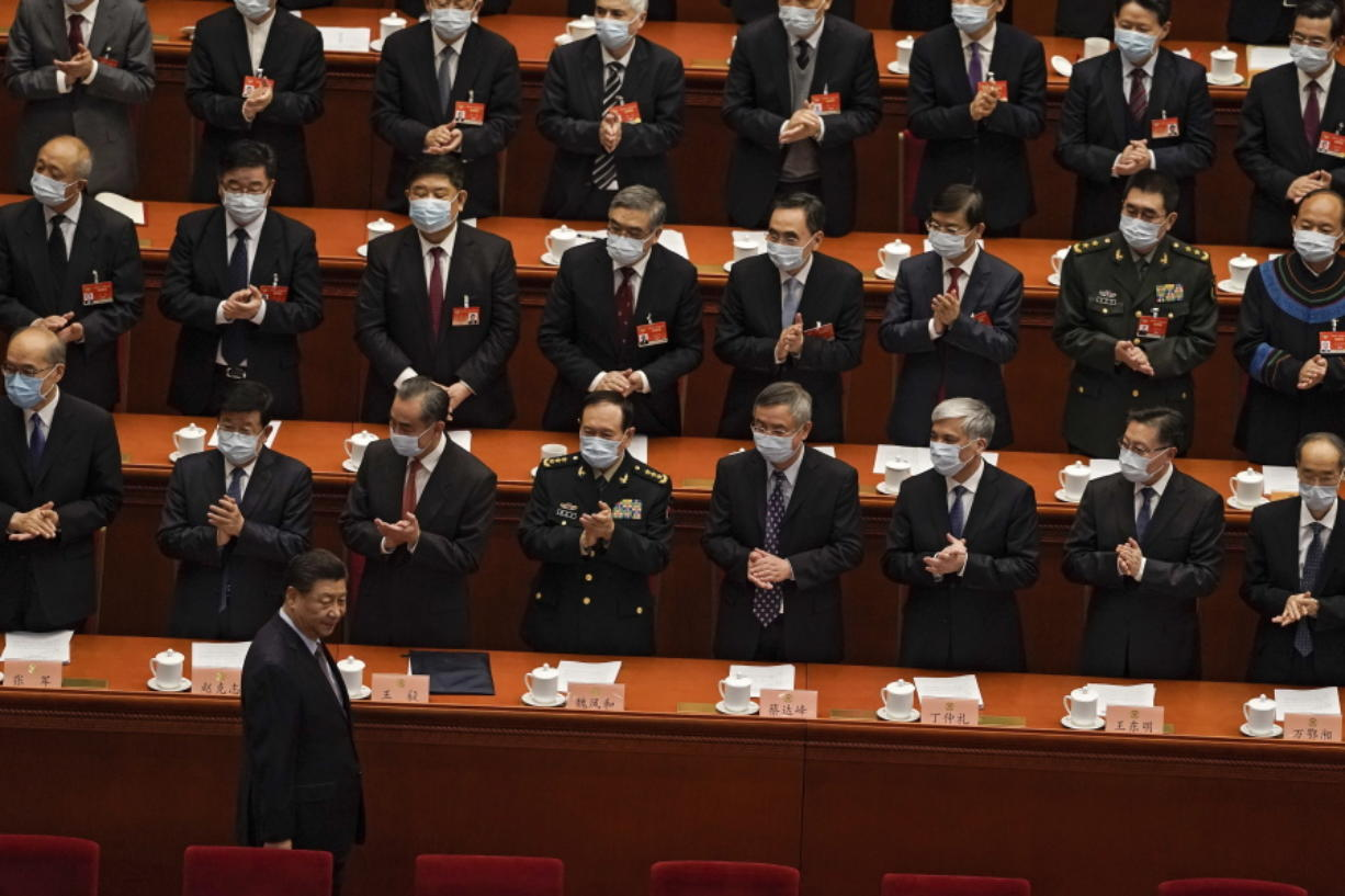 Delegates wearing face masks to help curb the spread of the coronavirus applaud as Chinese President Xi Jinping arrives for the opening session of Chinese People's Political Consultative Conference (CPPCC) at the Great Hall of the People in Beijing, Thursday, March 4, 2021.