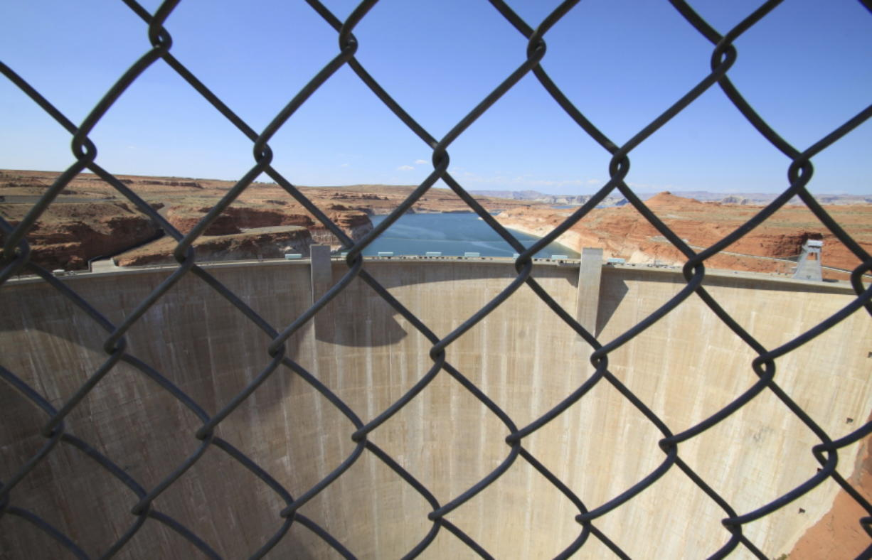 This Aug. 21, 2019 image shows Glen Canyon Dam beyond a chainlink fence near Page, Arizona. A plan by Utah could open the door to the state pursuing an expensive pipeline that critics say could further deplete the lake, which is a key indicator of the Colorado River's health.