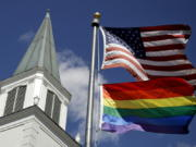 FILE - In this April 19, 2019 file photo, a gay pride rainbow flag flies along with the U.S. flag in front of the Asbury United Methodist Church in Prairie Village, Kan. Conservative leaders within the United Methodist Church unveiled plans Monday, March 1, 2021 to form a new denomination, the Global Methodist Church, with a doctrine that does not recognize same-sex marriage. The move could hasten the long-expected breakup of the UMC, America's largest mainline Protestant denomination, over differing approaches to LGBTQ inclusion.