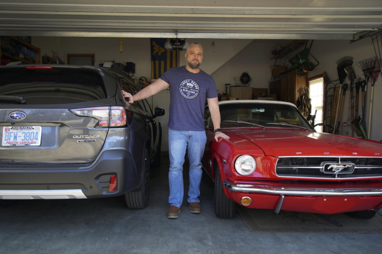 Steve Bock stands between his new Subaru Outback and his 1965 Ford Mustang at his home in Apex, N.C., on Friday, March 5, 2021. He would like to have an electric car, but says the prices will have to come down a lot before he can do it. Opinion polls show that most Americans would consider an EV if it cost less, if more charging stations existed and if a wider variety of models were available. (AP Photo/Allen G.