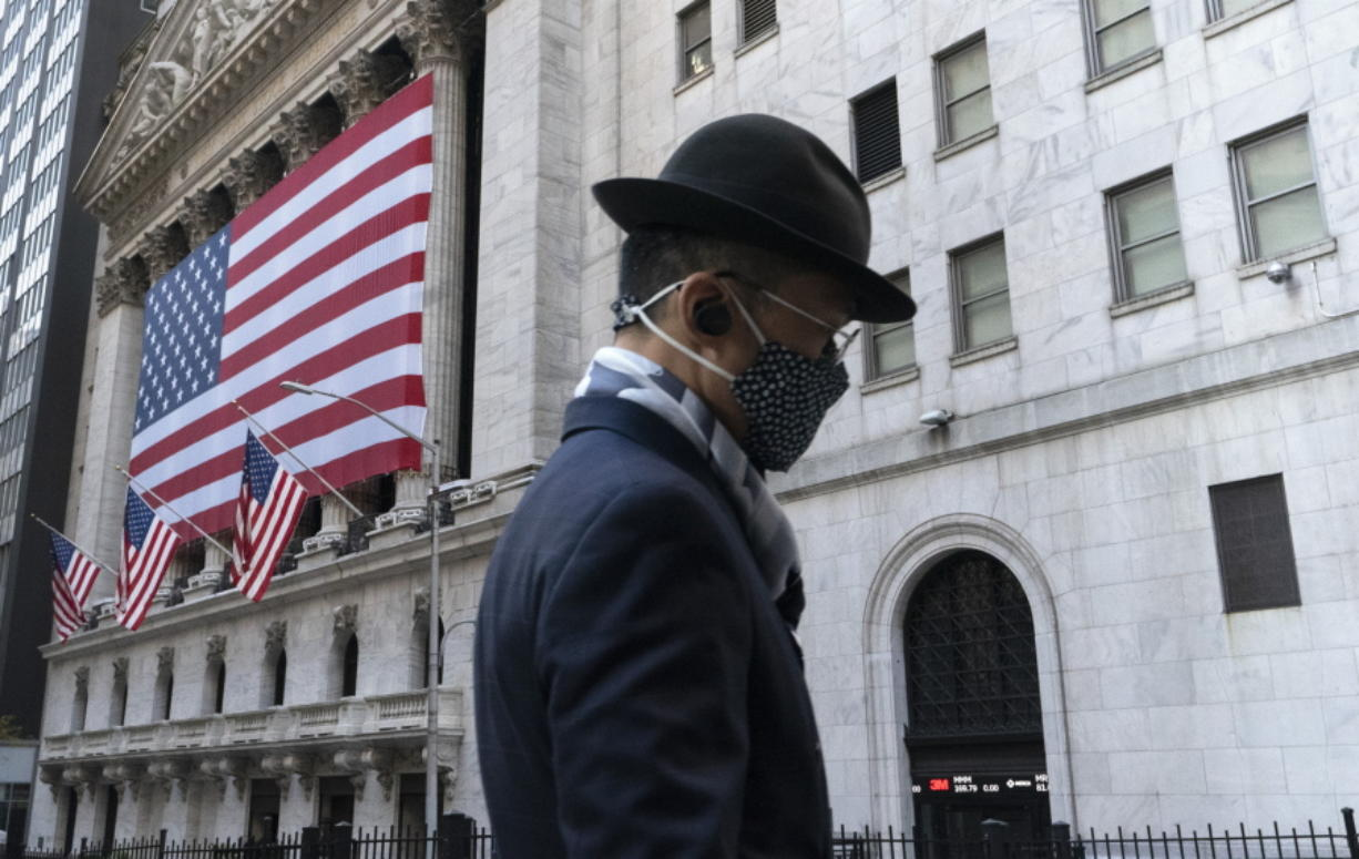 FILE - In this Nov. 16, 2020 file photo a man wearing a mask passes the New York Stock Exchange in New York. Stocks are moving modestly higher in early trading on Wall Street as investors cautiously welcome signs of calm in the bond market. The S&P 500 was up 0.4% early Thursday, March 4, 2021, and the yield on the 10-year Treasury held steady at 1.47%.