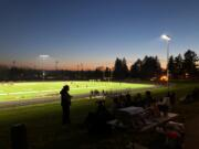 Fans sit on the berm north of the football field at Hudson's Bay High School on Friday. The Eagles beat R.A. Long 28-13 in the first varsity game on campus at the school, which was built in 1955.