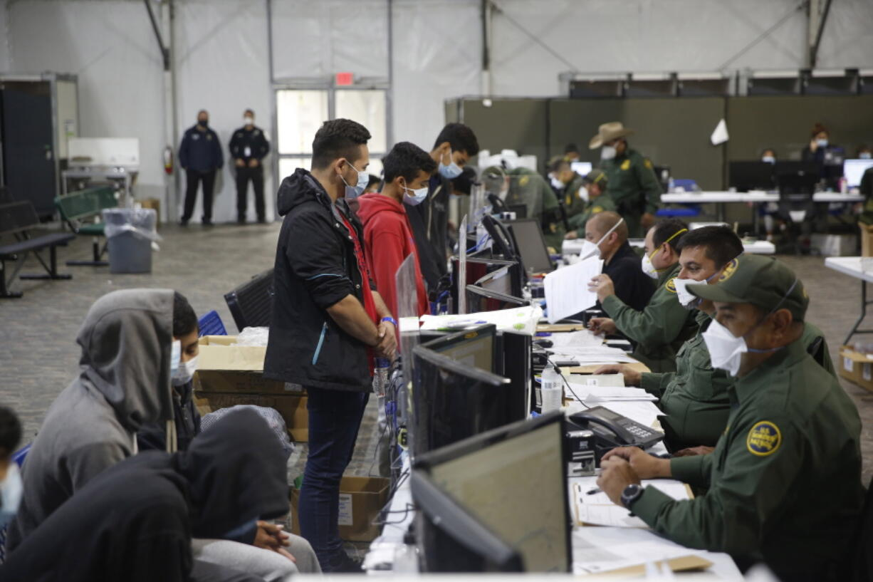 Migrants are processed at the intake area of the Donna Department of Homeland Security holding facility, the main detention center for unaccompanied children in the Rio Grande Valley, in Donna, Texas, Tuesday, March 30, 2021.