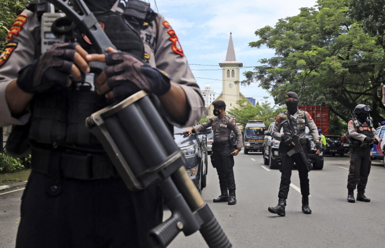 Police officers stand guard near a church where an explosion went off in Makassar, South Sulawesi, Indonesia, Sunday, March 28, 2021.