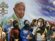 Women wait outside the Chaldean Cathedral of Saint Joseph, in Baghdad, Iraq, Saturday, March 6, 2021, where Pope Francis, depicted on a giant poster at their back, is concelebrating a mass. Earlier today Francis met privately with the country's revered Shiite leader, Grand Ayatollah Ali al-Sistani.