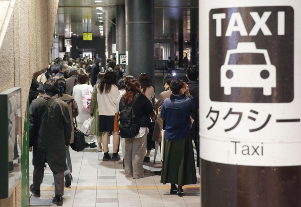 People queue up for taxi as train services are suspended following an earthquake in Sendai, Miyagi prefecture, Japan Saturday, March 20, 2021. A strong earthquake struck Saturday off northern Japan, shaking buildings even in Tokyo and triggering a tsunami advisory for a part of the northern coast.