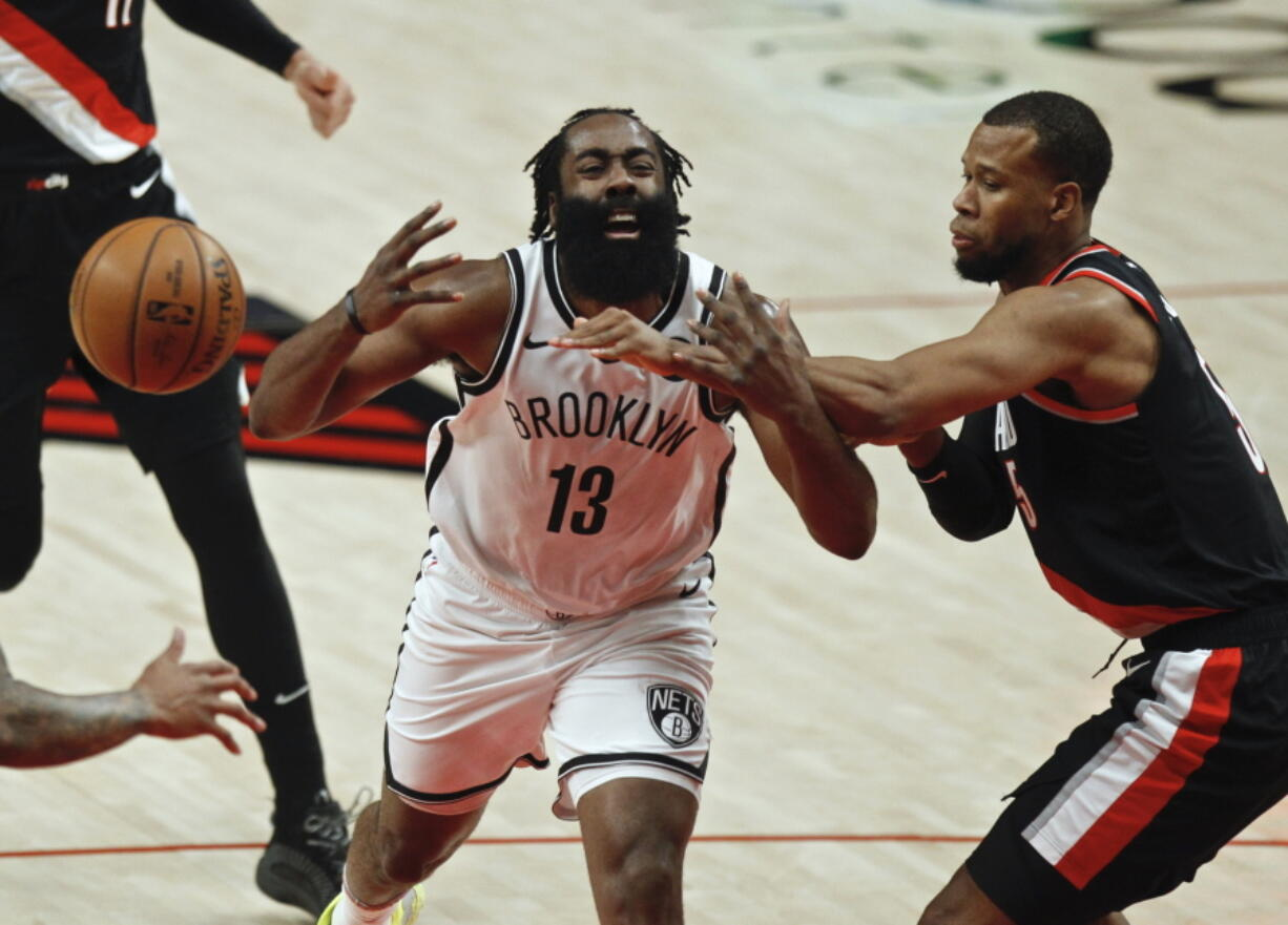 Brooklyn Nets guard James Harden, left, is fouled by Portland Trail Blazers guard Rodney Hood, right, during the first half of an NBA basketball game in Portland, Ore., Tuesday, March 23, 2021.