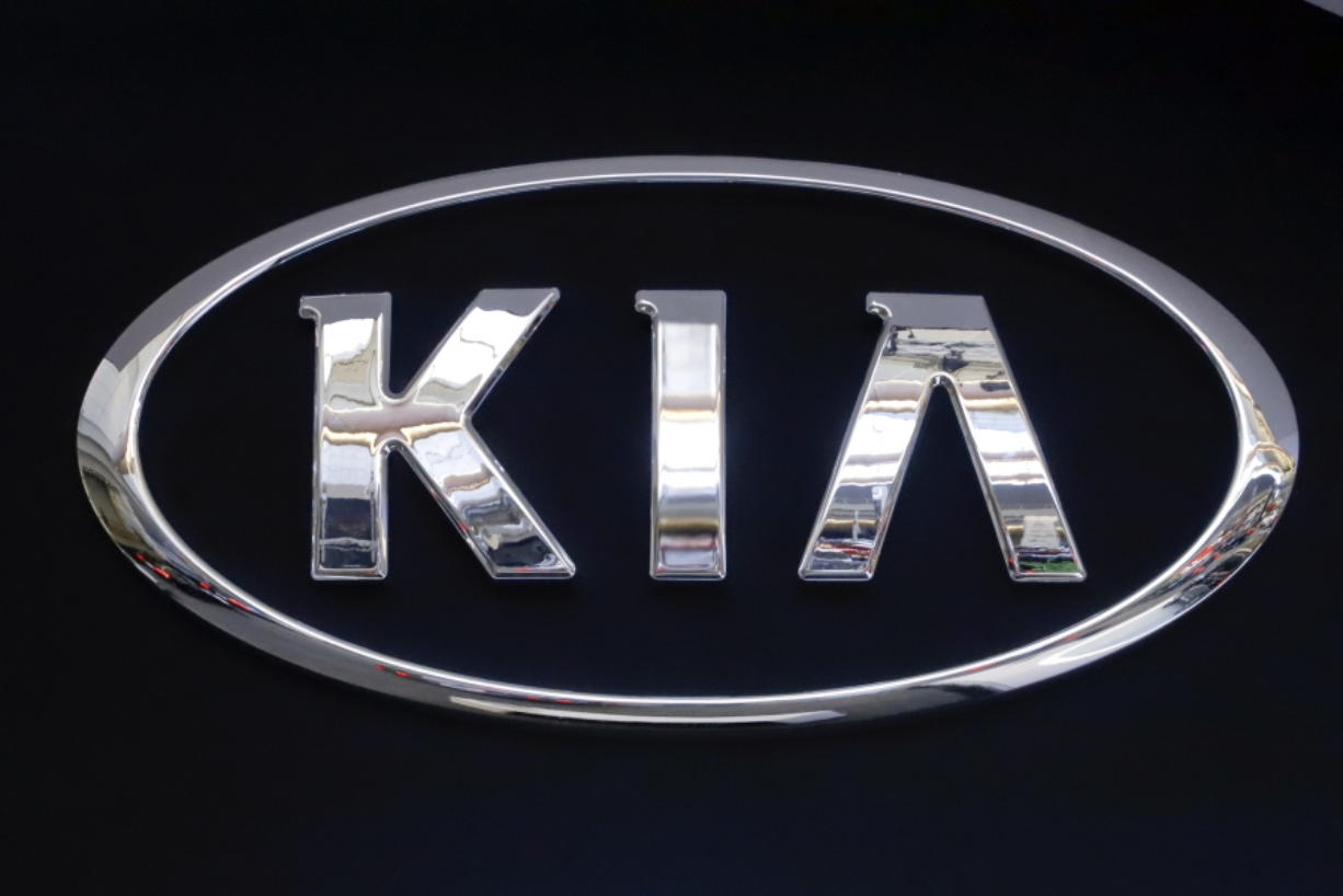FILE - In this Feb. 14, 2019 file photo, the KIA logo is displayed on a sign at the 2019 Pittsburgh International Auto Show in Pittsburgh. Kia is telling owners of nearly 380,000 vehicles in the U.S. to park them outdoors due to the risk of an engine compartment fire. The Korean automaker is recalling certain 2017 through 2021 Sportage SUVs and 2017 through 2019 Cadenza sedans to fix the problem. (AP Photo/Gene J.