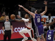 Portland Trail Blazers guard Damian Lillard, left, dives to the basket as Sacramento Kings forward Nemanja Bjelica defends during the first half of an NBA basketball game in Portland, Ore., Thursday, March 4, 2021.