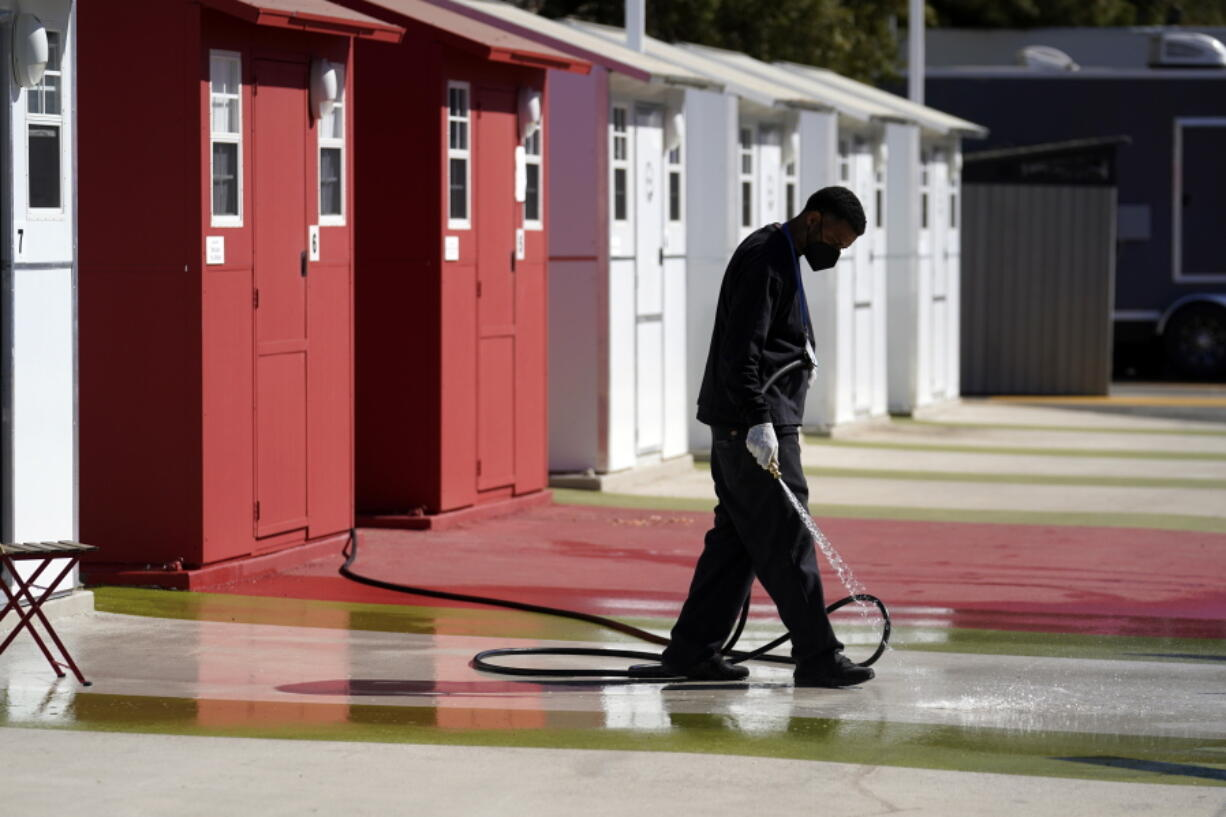 A worker cleans in front of a row of tiny homes for the homeless, Thursday, Feb. 25, 2021, in the North Hollywood section of Los Angeles.