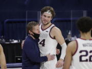 Gonzaga coach Mark Few, left, hugs forward Corey Kispert after Kispert, a senior playing his last home game, left the court near the end of the second half of the team's NCAA college basketball game against Loyola Marymount in Spokane, Wash., Saturday, Feb. 27, 2021. Gonzaga won 86-69.