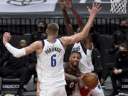 Portland Trail Blazers guard Damian Lillard, middle, passes the ball on Dallas Mavericks center Kristaps Porzingis, left, during the second half of an NBA basketball game in Portland, Ore., Sunday, March 21, 2021.