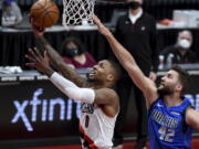 Portland Trail Blazers guard Damian Lillard, left, drives to the basket past Dallas Mavericks forward Maxi Kleber during the first half of an NBA basketball game in Portland, Ore., Friday, March 19, 2021.