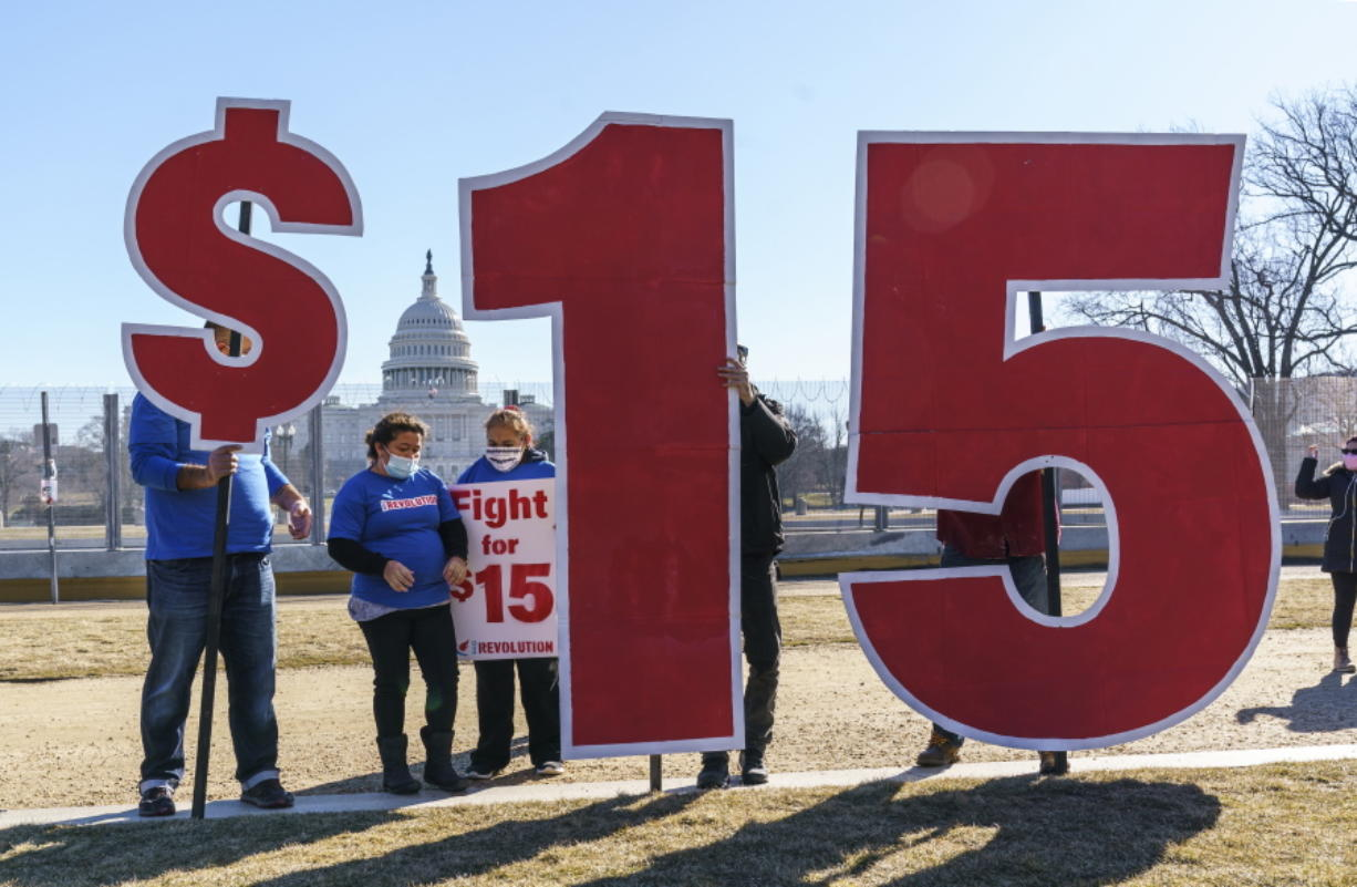 Activists appeal for a $15 minimum wage near the Capitol in Washington, Thursday, Feb. 25, 2021. The $1.9 trillion COVID-19 relief bill being prepped in Congress includes a provision that over five years would hike the federal minimum wage to $15 an hour. (AP Photo/J.