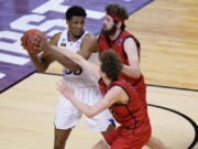 Kansas forward David McCormack, left, is pressured by Eastern Washington forward Tanner Groves, right, and teammate Eastern Jacob Groves, bottom, during the second half of a first-round game in the NCAA college basketball tournament at Farmers Coliseum in Indianapolis, Saturday, March 20, 2021.