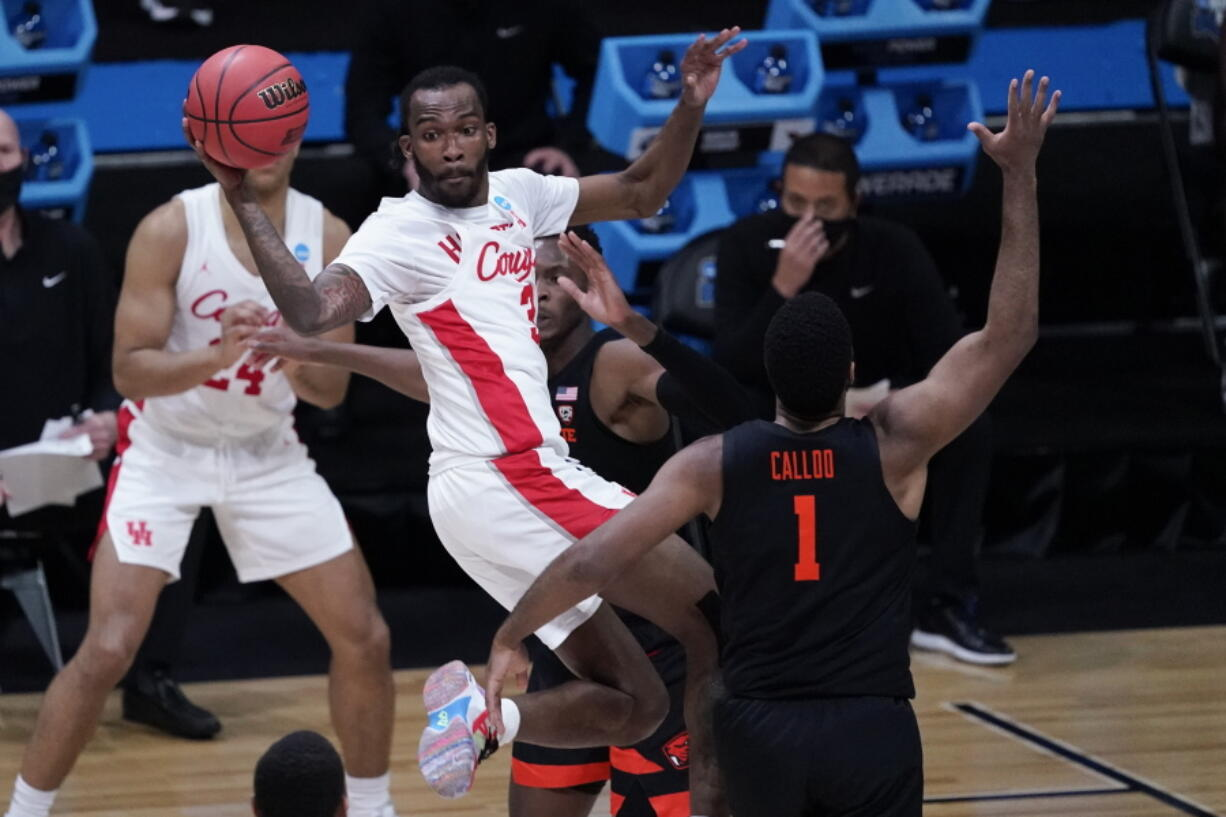 Houston guard DeJon Jarreau (3) passes over Oregon State forward Maurice Calloo (1) during the first half of an Elite 8 game in the NCAA men's college basketball tournament at Lucas Oil Stadium, Monday, March 29, 2021, in Indianapolis.
