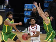 Southern California guard Tahj Eaddy (2) drives between Oregon guard LJ Figueroa, left, and guard Will Richardson, right, during the first half of a Sweet 16 game in the NCAA men's college basketball tournament at Bankers Life Fieldhouse, Sunday, March 28, 2021, in Indianapolis.