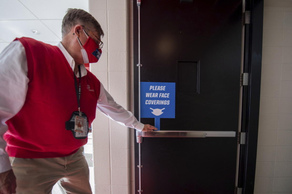 An usher places a sign near the fans' entrance to remind them to wear face coverings for a first-round game in the NCAA men's college basketball tournament, Saturday, March 20, 2021, at Assembly Hall in Bloomington, Ind.