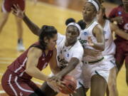Washington State forward Ula Motuga (15), left, drives against South Florida forward Bethy Mununga (20), center, and South Florida center Shae Leverett (21), right, during the second quarter of a college basketball game in the first round of the women's NCAA tournament at the Frank Erwin Center in Austin, Texas, Sunday, March 21, 2021. (Ricardo B.