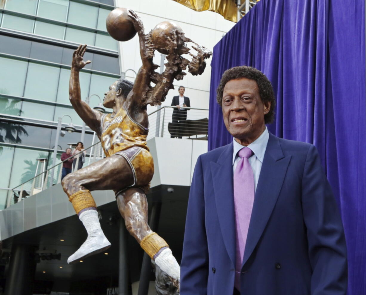 FILE - Elgin Baylor stands next to a statue, just unveiled, honoring the Minneapolis and Los Angeles Lakers great, outside Staples Center in Los Angeles, in this Friday, April 6, 2018, file photo. Elgin Baylor, the Lakers' 11-time NBA All-Star, died Monday, March 22, 2021, of natural causes. He was 86. The Lakers announced that Baylor died in Los Angeles with his wife, Elaine, and daughter Krystal by his side.