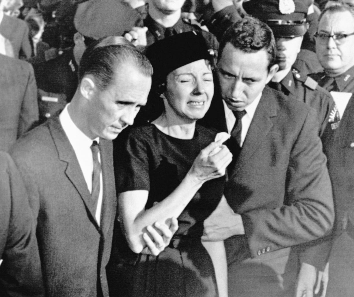 FILE - In this Monday, Nov. 25, 1963, file photo, Marie Tippit, widow of police officer J.D. Tippit who was slain during the search for President John F. Kennedy's assassin, is led weeping from Beckley Hills Baptist Church in Dallas after funeral services for her husband. Tippit who was a 35-year-old mother of three when her husband, Officer J.D. Tippit, was killed on Nov. 22, 1963, has died at age 92. Her son said she died Tuesday, March 2, 2021, at a hospital in the East Texas city of Sulphur Springs after being diagnosed with pneumonia following a positive test for COVID-19.