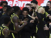 Oregon's Aaron Estrada, center, and teammates celebrate their team's win over Oregon State and their second consecutive Pac-12 regular-season conference title following an NCAA college basketball game in Corvallis, Ore., Sunday, March 7, 2021.