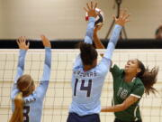 "FILE - Reagan's Kyla Waiters, right, spikes the ball past Johnson defenders during a Texas District 26-6A high school volleyball match in San Antonio, Texas, in this Friday, Sept. 22, 2017, file photo. Oregon State leaders are suing to block disclosure of details about an investigation of abuse allegations in their volleyball program, even as they tout a refreshed mission for transparency in wake of their president's resignation over the handling of sexual-misconduct cases at another school. ""I'm guessing there's something in those records that they don't want out,"" said Dorina Waiters, whose daughter, Kyla, left Oregon State after a year on the volleyball team triggered depression that led to suicidal thoughts."