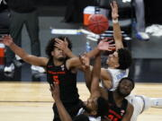 Oregon State's Ethan Thompson, clockwise from top left, UCLA's Jules Bernard, Oregon State's Rodrigue Andela, and UCLA's Cody Riley (2) vie for a rebound during the second half of an NCAA college basketball game in the quarterfinal round of the Pac-12 men's tournament Thursday, March 11, 2021, in Las Vegas.