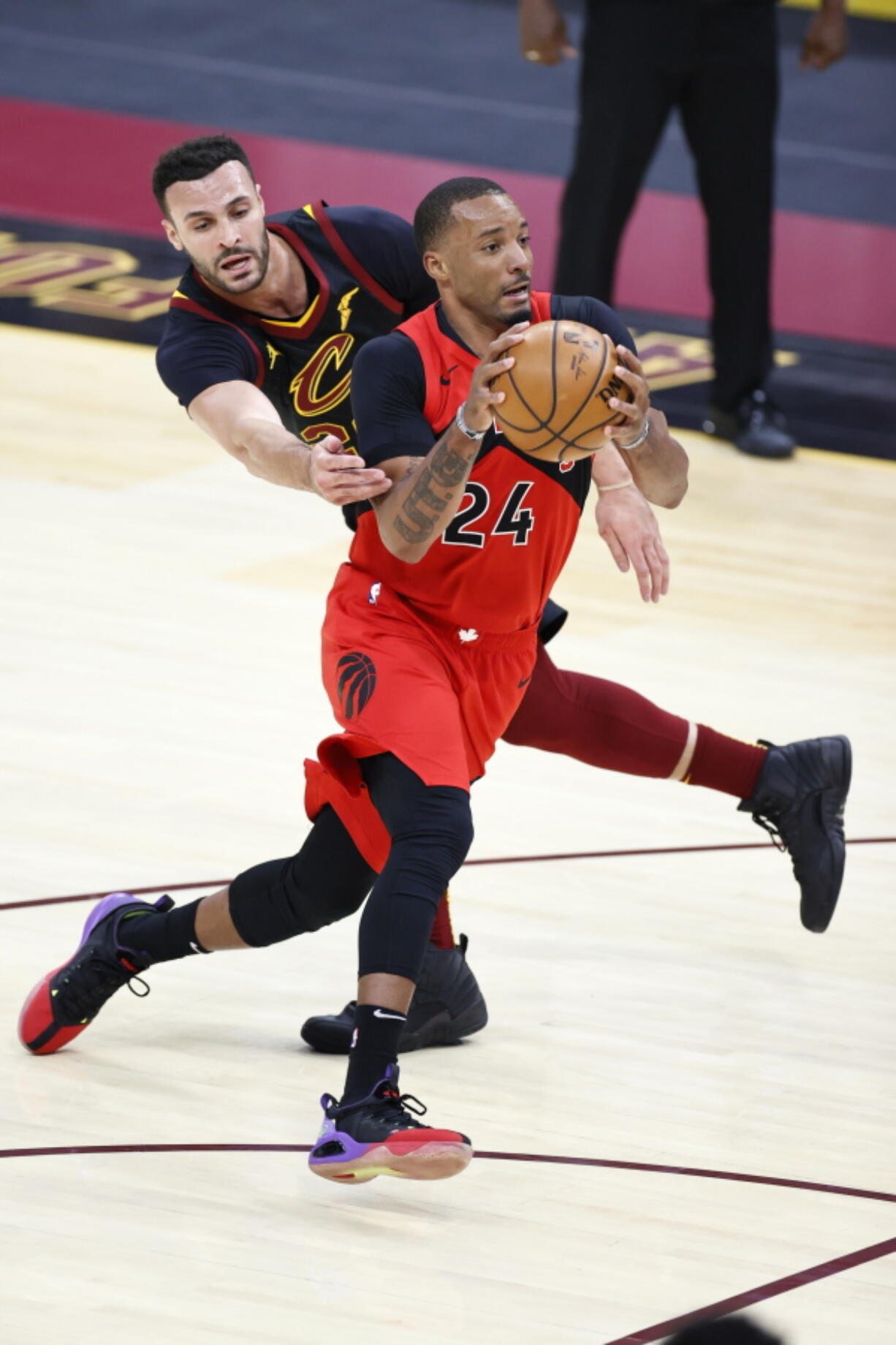 Toronto Raptors' Norman Powell (24) drives past Cleveland Cavaliers' Larry Nance Jr. (22) in the second half of an NBA basketball game, Sunday, March 21, 2021, in Cleveland.
