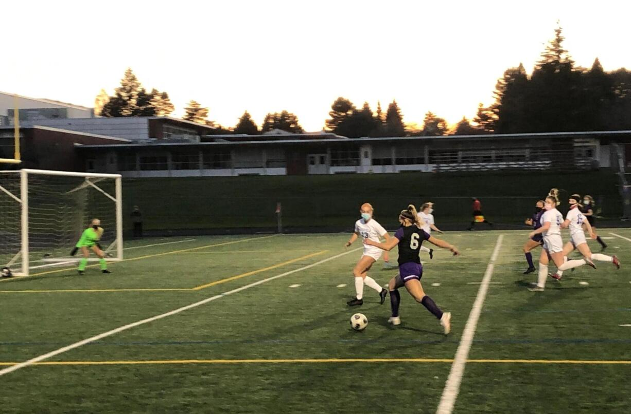 Columbia River forward Maree Seibel advances toward the goal while Cameron Jones of Ridgefield defends during a 2A district playoff game Tuesday at Columbia River High School.