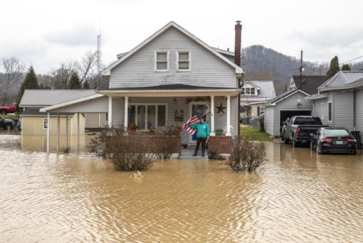 Catherine Castle stands on the porch of her home in downtown Paintsville, Ky., as floodwaters approach on Monday, March 1, 2021.  (Ryan C.