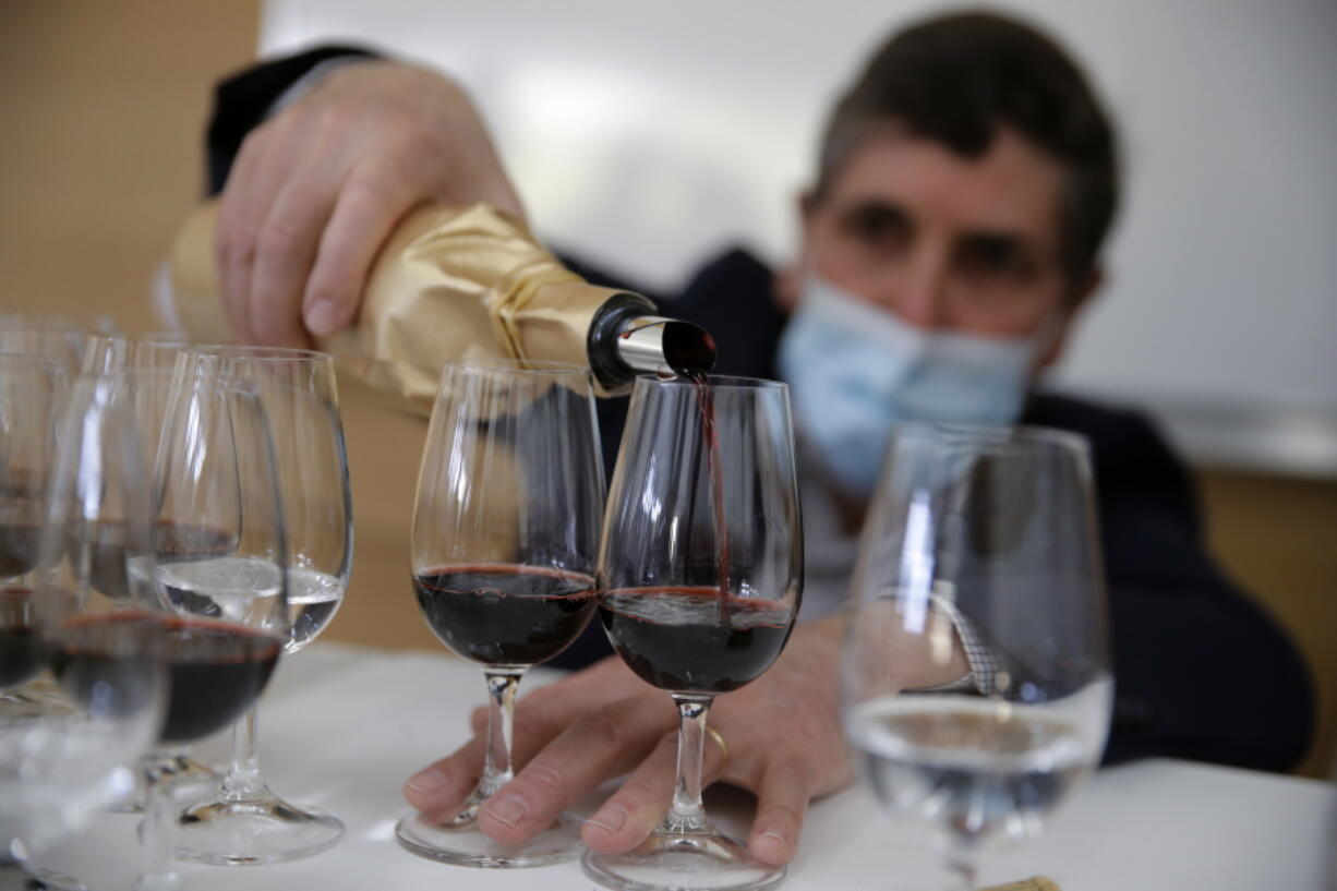 Philippe Darriet, president of the Institute for Wine and Vine Research and head oenologist fills glasses with wine for a blind tasting March 1 at the ISVV Institute in Villenave-d'Ornon, southwestern France.