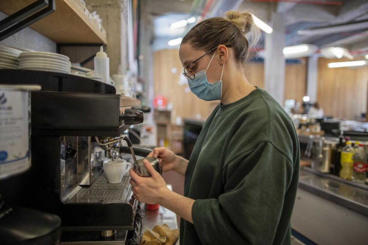 Waiter Sara Palacios prepares a coffee as she works at La Francachela restaurant in Madrid, Spain, Friday, March 26, 2021.