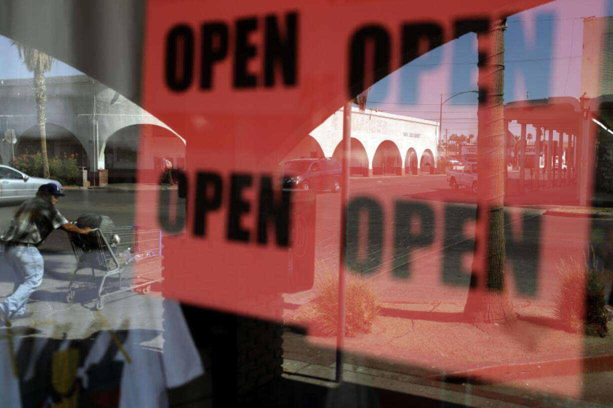 ADVANCE FOR RELEASE MARCH 14, 2021, AND THEREAFTER - FILE - In this June 30, 2020, photo, a man passes a clothing shop with open signs in the window in Calexico, Calif. A year after the first coronavirus shutdowns, many U.S. states and cities are still struggling with a silent side effect: Public records have become harder to get. As states prepared to reopen their economies following coronavirus shutdowns last spring, The Associated Press asked governors across the U.S. for records that could shed light on how businesses and health officials influenced their decisions.