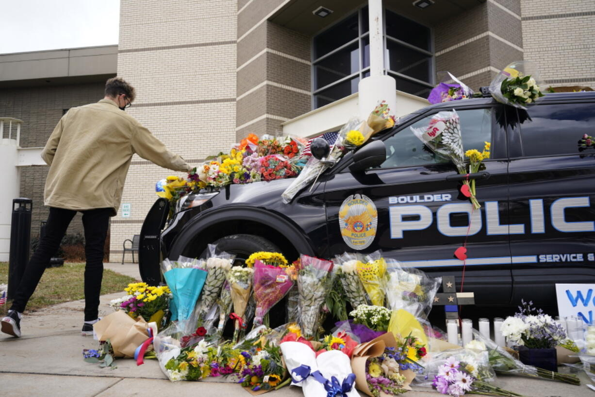 In this March 23, 2021, photo, a man leaves a bouquet on a police cruiser parked outside the Boulder Police Department after an officer was one of the victims of a mass shooting at a King Soopers grocery store in Boulder, Colo. The suspects in the most recent shooting sprees found it relatively easy to get their guns.