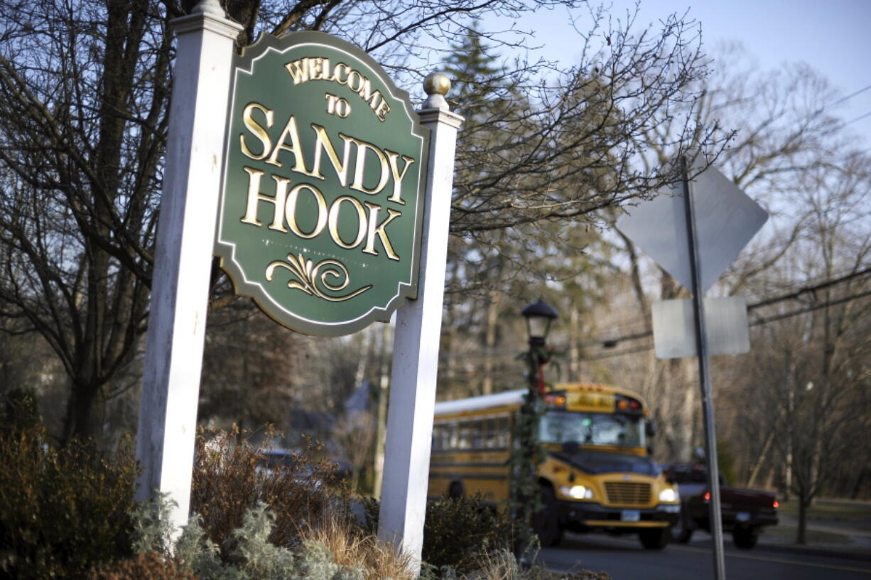 FILE - In this Dec. 4, 2013, file photo, a school bus drives past a sign reading Welcome to Sandy Hook, in Newtown, Conn., where 26 people were killed by a gunman inside Sandy Hook Elementary School. Students who were planning to attack schools showed the same types of troubled histories as those who carried them out - they were badly bullied, often suffered from depression with stress at home, and their behavior worried others, according to a U.S.