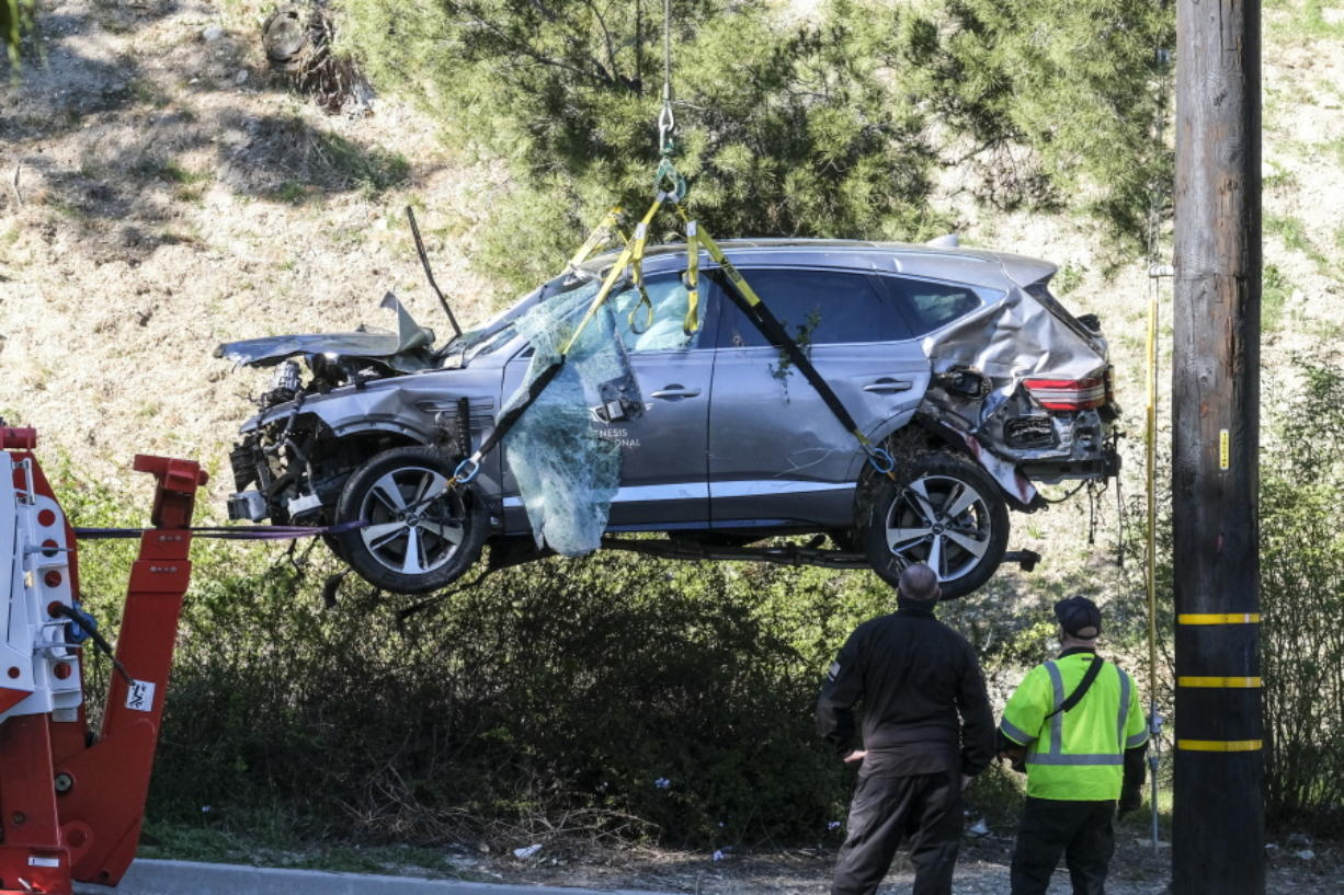 """FILE - In this Feb. 23, 2021, file photo, a crane is used to lift a vehicle following a rollover accident involving golfer Tiger Woods, in the Rancho Palos Verdes suburb of Los Angeles. Detectives are looking at data from the so-called """"black box"""" of Tiger Woods' SUV to get a clearer picture of what occurred during the Southern California rollover crash last week that seriously injured the golf star, authorities said Wednesday, March 3. (AP Photo/Ringo H.W."""