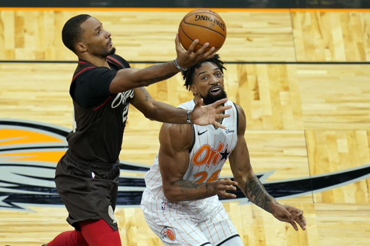 Portland Trail Blazers Norman Powell, left, goes up to shoot past Orlando Magic center Khem Birch during the first half of an NBA basketball game, Friday, March 26, 2021, in Orlando, Fla.