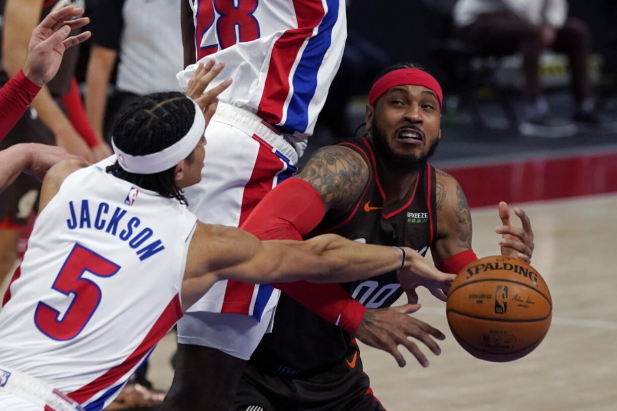 Portland Trail Blazers forward Carmelo Anthony is fouled by Detroit Pistons center Isaiah Stewart (28) as Detroit Pistons guard Frank Jackson (5) knocks the ball away during the first half of an NBA basketball game, Wednesday, March 31, 2021, in Detroit.