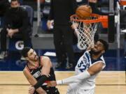 Minnesota Timberwolves center Karl-Anthony Towns dunks past Portland Trail Blazers center Enes Kanter Sunday in Minneapolis.